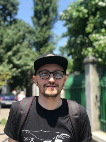 Alin Halațiu, gazda eveniment, organizator, bărbat cu ochelari, șapca și barbă, păr scurt, zâmbește