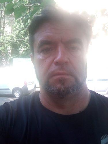 George, agent pază, bărbat, poartă cioc, riduri adânci pe frunte, părul tuns scurt, maxilare pătrate