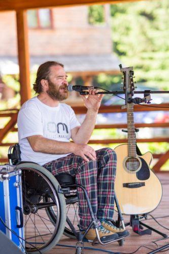 Florin Mândru, artis folk, utilizator de scaun rulant, păr mediu, pieptănat pe spate, început de chelie în partea din față, barbă lungă și deasă, vârstă medie