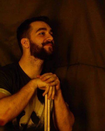 Bărbat cu barbă, privește într-o parte, zâmbește, se sprijină în bețele pentru tobe