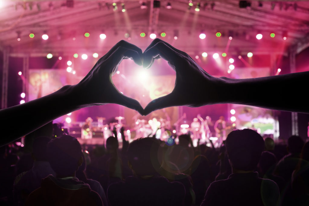 Mulțime de oameni la concert cu două mâini ce formează o inimă în prim plan. Umbra unui bărbat și a unei femei