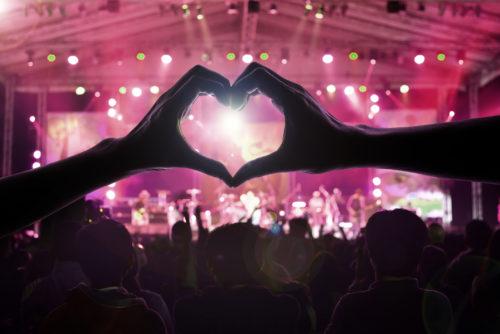 Mulțime de oameni la concert cu doămâini ce formează o inimă în prim plan. Umbra unui bărbat și a unei femei