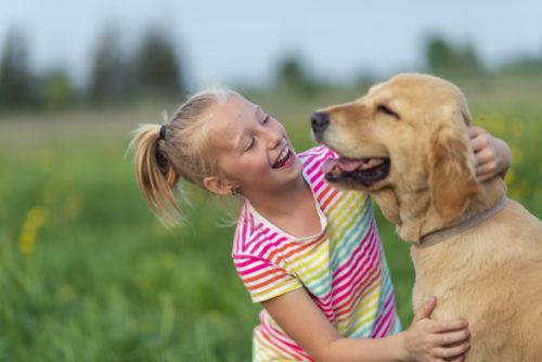 o fetiță zâmbește și se joaca cu un câine cu mult drag. Este afară, pe iarbă, într-o zi cu soare.