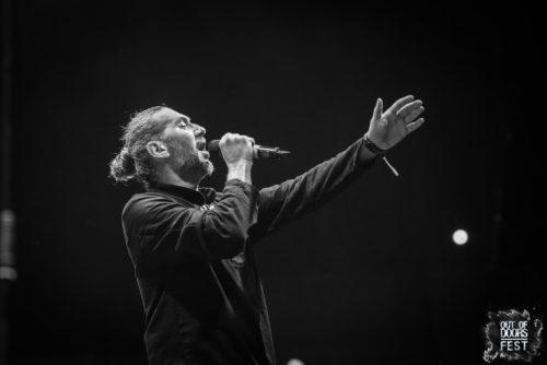 bărbat pe scenă, are părul prins în coadă, cânta la un microfon