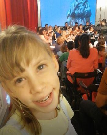 fată zâmbind fericită, în prim plan, are breton și cercei lungi, cu ciucuri. Este într-o sală de concert, în spatele ei se vede orchestra, cântând. Sunt oameni în sală, așezați pe scaune