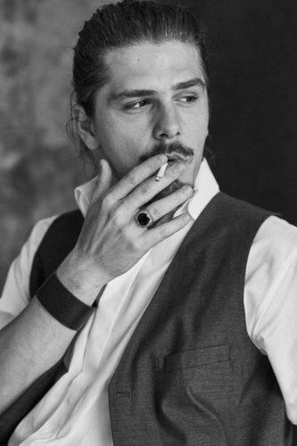 bărbat, are părul lung prins în coadă, poartă cioc, fumează poartă un inel în deget