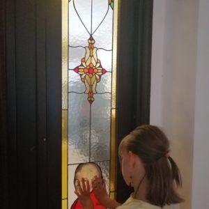 Fetiță ce mângâie cu degetele o fereastră cu vitralii