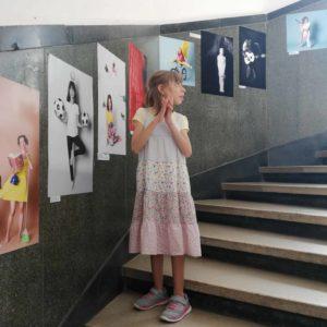 Fata de unsprezece ani coborând o scară în spirală dintr-o clădire veche. Pe peretele din dreapta ei sunt fotografii ale altor copii