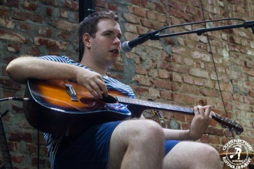 tânăr pe scenă, stă pe scaun, în fața sa este un microfon, cântă la chitară