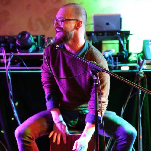 bărbat ras în cap, poarta barbă și ochelari, sta pe o scenă și bate la tobă