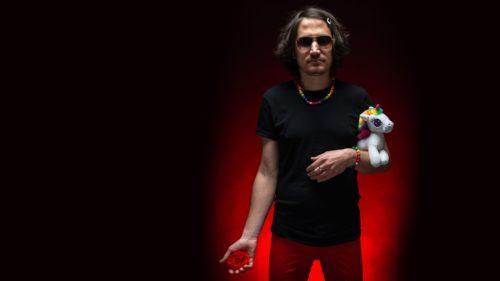 bărbat, păr lung mediu, poartă ochelari, în brațe ține un unicorn de pluș