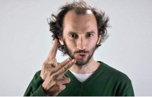 bărbat, are barbă scurtă, păr ciufulit, în partea din fața are chelie. Cu ambele mâini interpretează ceva în limbajul semnelor.