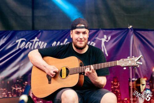 bărbat, în mână ține o chitară, poartă șapcă cu cozorocul întors la spate, pielea mâinilor este ca după o arsură