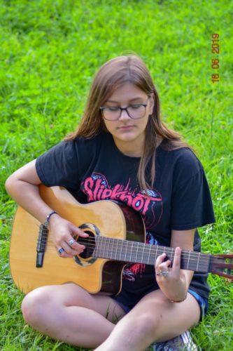 fata tânără, păr lung si ochelari, c~nta la chitară, poartă mai multe inele