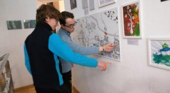 doi băieți adolescenți privesc o lucrare de grafică expusă pe perete. Lucrarea reprezintă harta orașului Brăila, amândoi zâmbesc și urmăresc cu degetul informațiile de pe desen