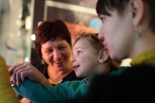 portret al unei familii fericite în muzeu. mama, bunica și un copil. Bunica ridică mâna copilului, ajutându-l să atingă un obiect