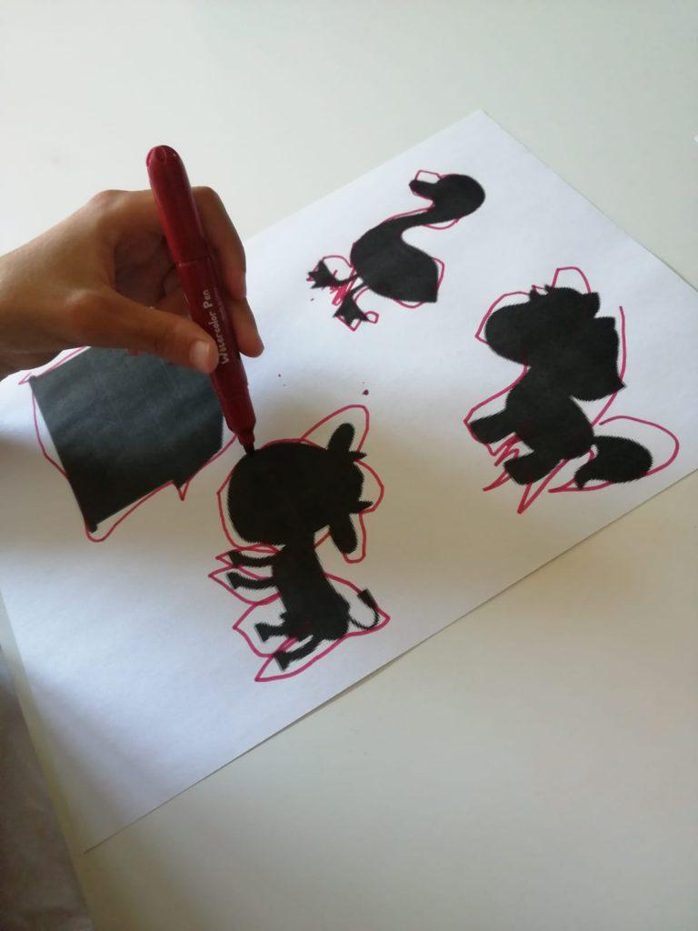 umbre ale unor animale de curte, printate de o foaie, o mână de copil trasează conturul lor, cu o cariocă, stângaci