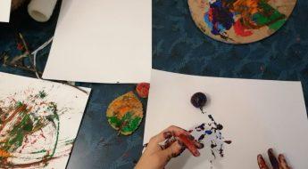 o masă. pe masă sunt foi și culori pentru pictură. Se observă două mâini mici, ce țin o pensulă făcută din crenguțe și iarbă. Pictează