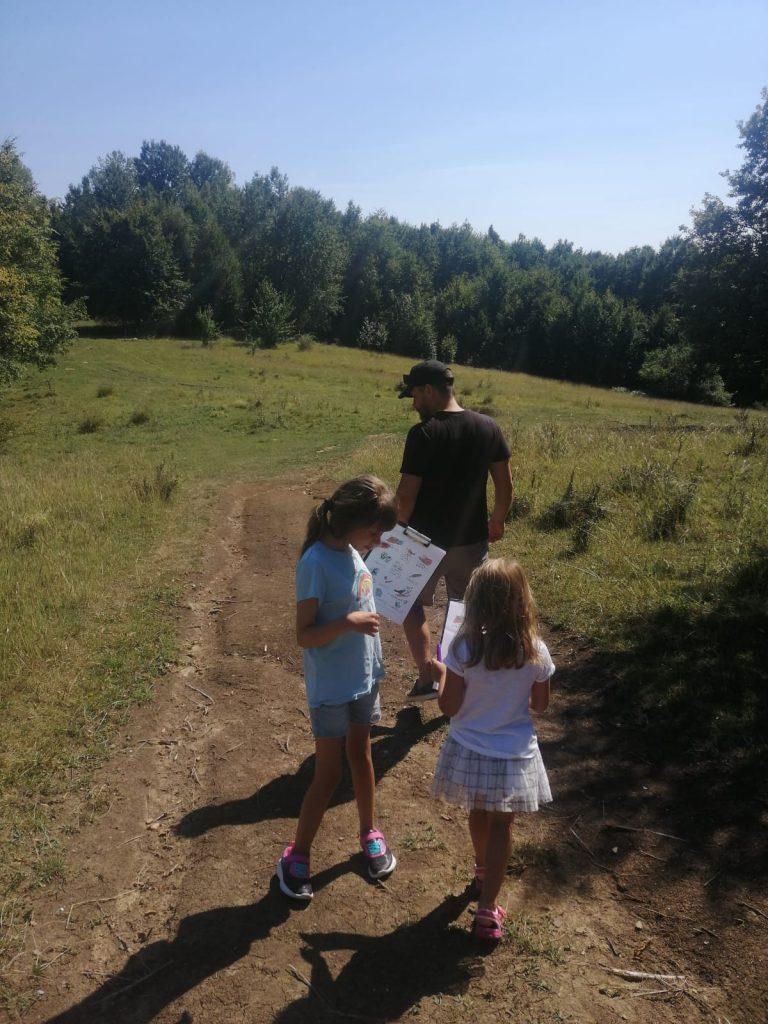 """două fete împreună cu tatăl lor pe un drum în marginea pădurii. Fetele țin în mână foi pe care sunt printate activități de tipul """"ce auzi, ce vezi"""""""