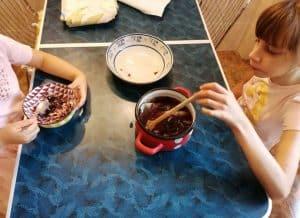 două fetițe la masa din bucătărie, se joacă cu frunze, plante, desenează
