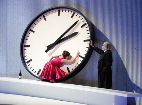 Imagine din spectacolul La Traviata.O scenă goală, un ceas supradimensionat sprijinit de perete. Un bătrân îmbrăcat în frac mișcă limbile ceasului. O femeie frumoasă, cu rochie de seară atinge ceasul